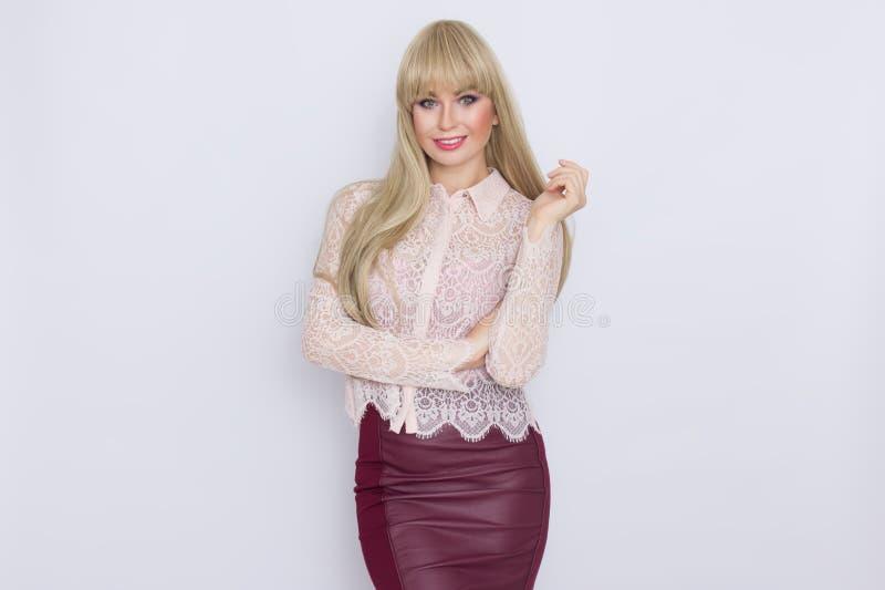 Portret romantyczna blondynki kobieta w różowej bluzce i zmroku - czerwieni spódnica zdjęcie royalty free