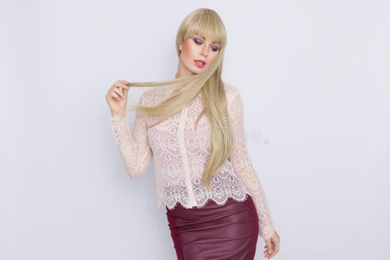 Portret romantyczna blondynki kobieta w różowej bluzce i zmroku - czerwieni spódnica fotografia royalty free