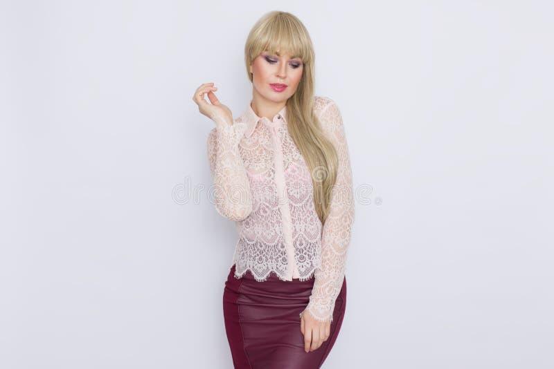 Portret romantyczna blondynki kobieta w różowej bluzce i zmroku - czerwieni spódnica fotografia stock