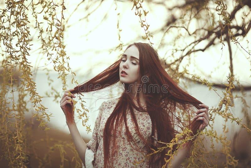 Portret romantyczna dziewczyna z czerwonym włosy w wiatrze pod wierzbowym drzewem zdjęcia royalty free