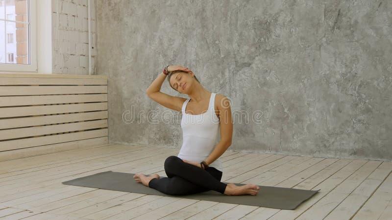 Portret rozciąga jej szyję i patrzeje daleko od przy joga klasą dojrzała kobieta obrazy stock