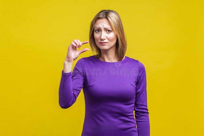 Portret rozczarowanej kobiety, ukazujący trochę gestu studio w pomieszczeniach wystrzelone na żółtym tle zdjęcia stock