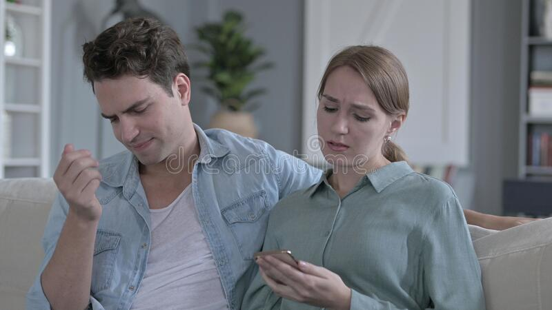 Portret rozczarowanej pary denerwującej się podczas korzystania ze smartfona obraz stock