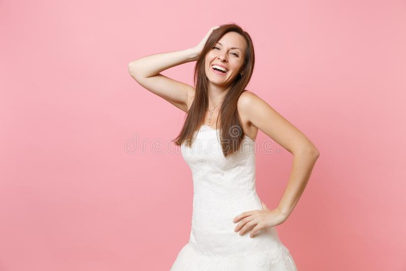 Portret roześmiana panny młodej kobieta w pięknej białej ślubnej sukni pozycji i utrzymywać ręki głowę odizolowywająca na menchia zdjęcie royalty free