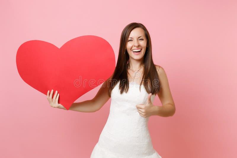 Portret roześmiana radosna panny młodej kobieta w pięknej białej ślubnej sukni pokazuje kciuk w górę i trzyma pustą pustą czerwie zdjęcia stock