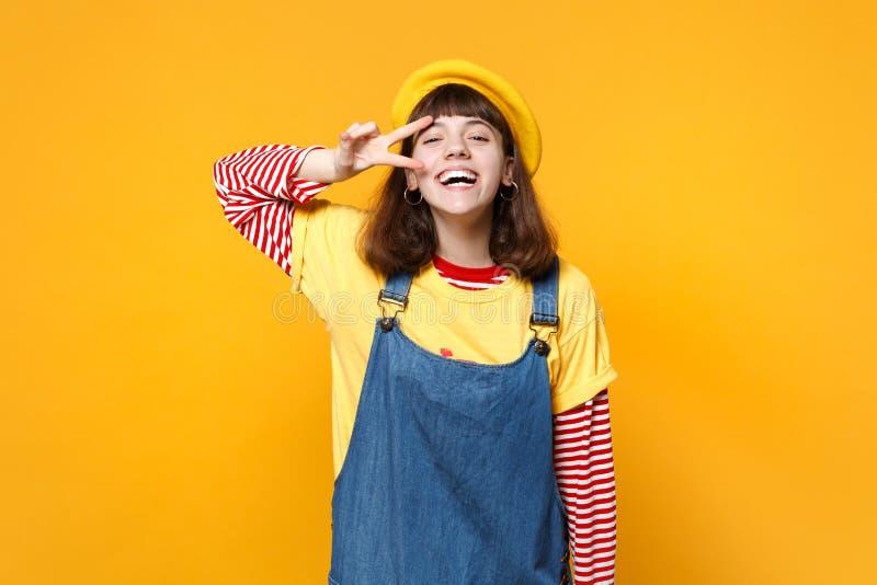 Portret roześmiany dziewczyna nastolatek w francuskim berecie, drelichowi sundress pokazuje zwycięstwo znaka odizolowywającego na obrazy stock