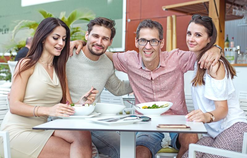 Portret rozochoceni przyjaciele w lato restauraci obrazy stock