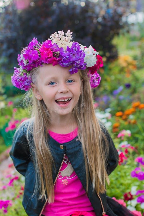 Portret rozochocona dziewczyna z wiankiem kwiaty na ona kierownicza obrazy stock