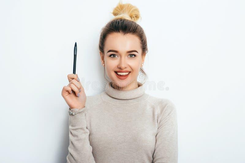 Portret rozochocona kobieta z interesującym uśmiechem, mieć włosianą babeczkę w pulowerze odizolowywającym na białym tła mienia p zdjęcie royalty free
