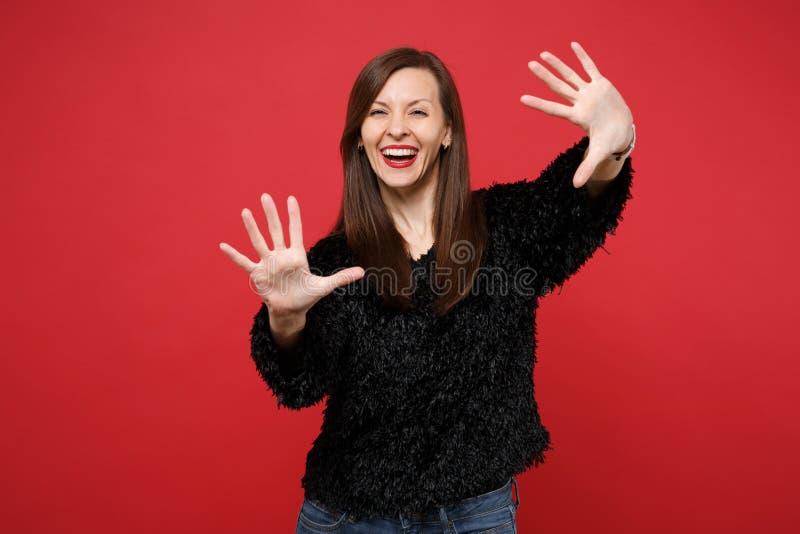Portret rozochocona młoda kobieta w czarnej futerkowej pulower pozycji pokazuje palmy na kamerze odizolowywającej na jaskrawej cz zdjęcia stock