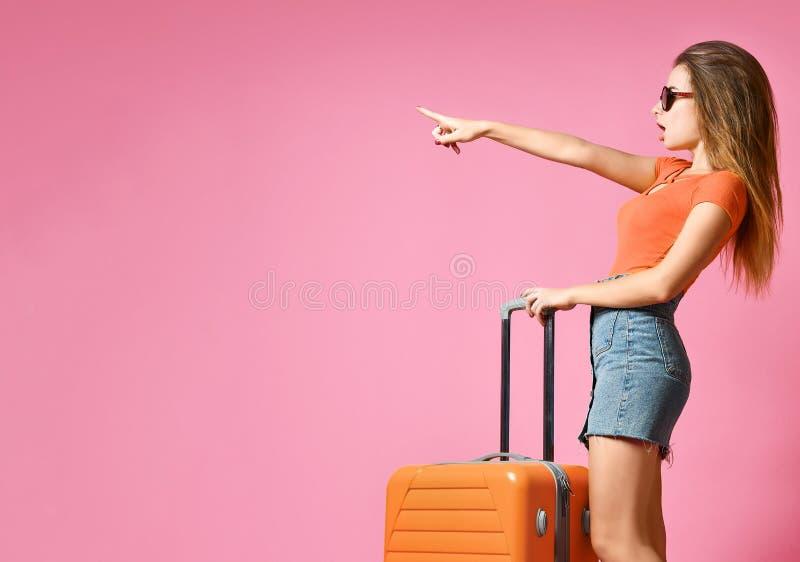 Portret rozochocona młoda caucasian kobieta ubierał w lat ubraniach z walizką i wskazywać palcowy oddalonego, zdjęcie royalty free