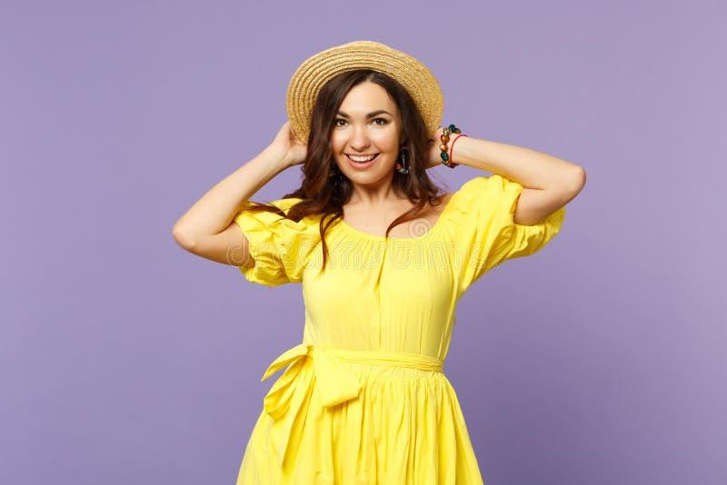 Portret rozochocona młoda kobieta w kolor żółty sukni kładzenia rękach na lato kapeluszu, przyglądająca kamera odizolowywająca na zdjęcia stock