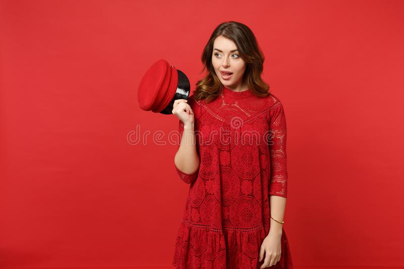 Portret rozochocona młoda kobieta w koronki sukni chwyta nakrętce pokazuje jęzor odizolowywającego na jaskrawej czerwieni ścianie zdjęcie stock