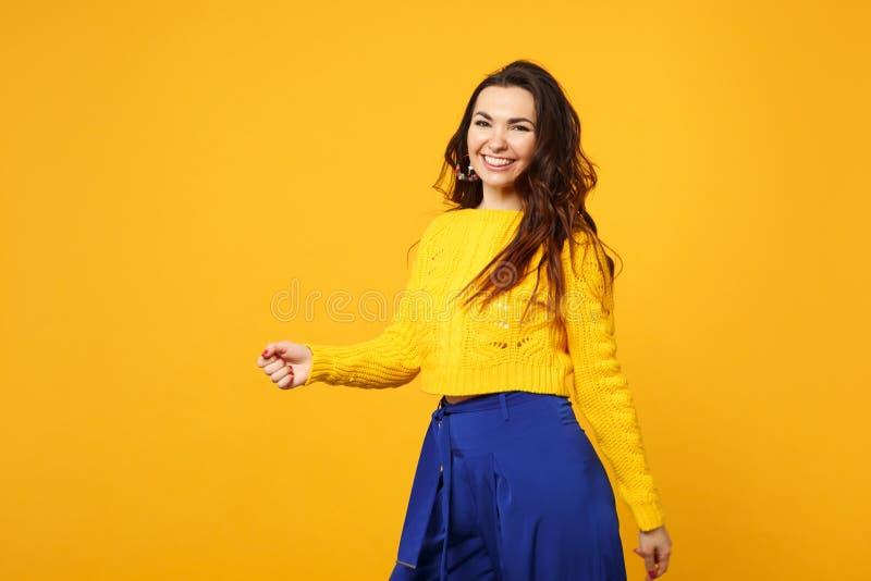 Portret rozochocona młoda kobieta w pulowerze, błękitna spodniowa pozycja, przyglądająca kamera na żółtej pomarańcze ścianie obrazy royalty free