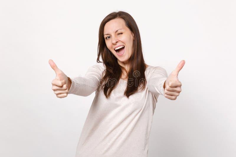 Portret rozochocona mruganie młoda kobieta patrzeje kamerę pokazuje aprobaty odizolowywać na biel ścianie w świateł ubraniach zdjęcia stock