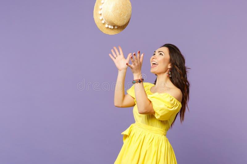 Portret rozochocona powabna młoda kobieta w koloru żółtego smokingowy rzucać w górę lato kapeluszu na pastelowej fiołek ścianie obraz royalty free