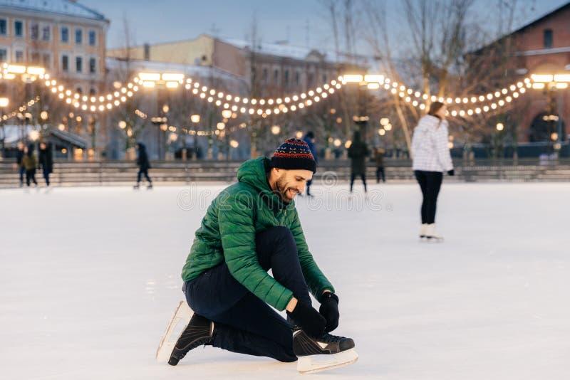 Portret rozochocona samiec zasznurowywa up łyżwy iść iść jeździć na łyżwach jak zdjęcia stock