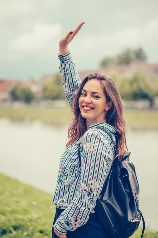 Portret rozochocona uśmiechnięta dziewczyna podczas gdy chodzący outdoors i machający rękę zdjęcie stock