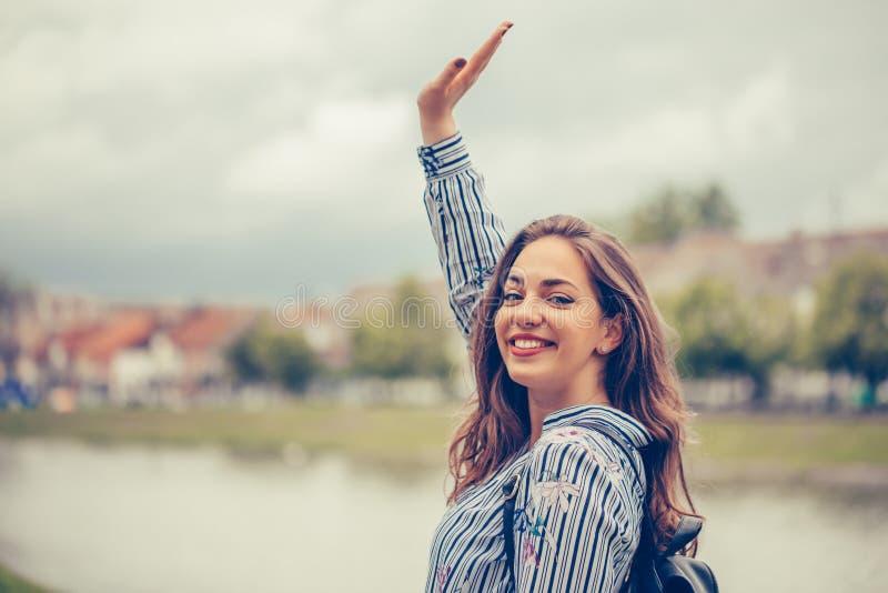 Portret rozochocona uśmiechnięta dziewczyna podczas gdy stojący outdoors i machający rękę fotografia stock