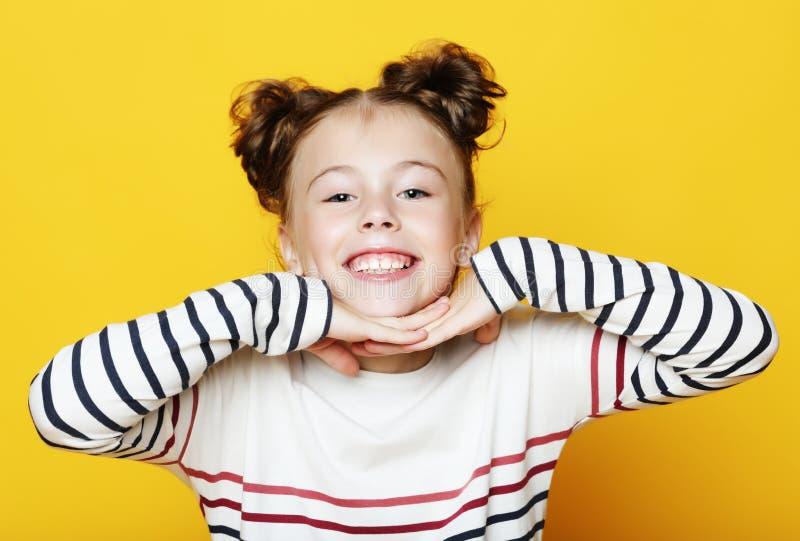 Portret rozochocona uśmiechnięta mała dziewczynka na żółtym tle zdjęcie royalty free