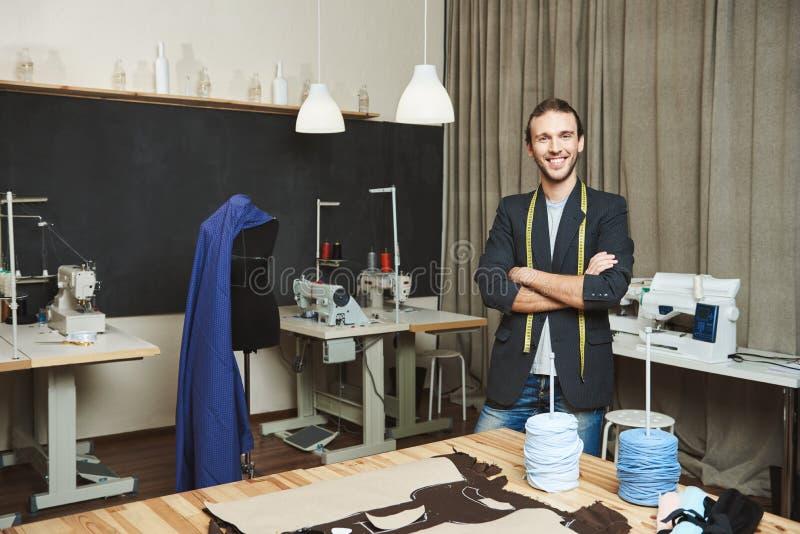 Portret rozochocony atrakcyjny męski odzieżowy projektant z ciemnym włosy w modnej strój pozyci w warsztacie fotografia stock