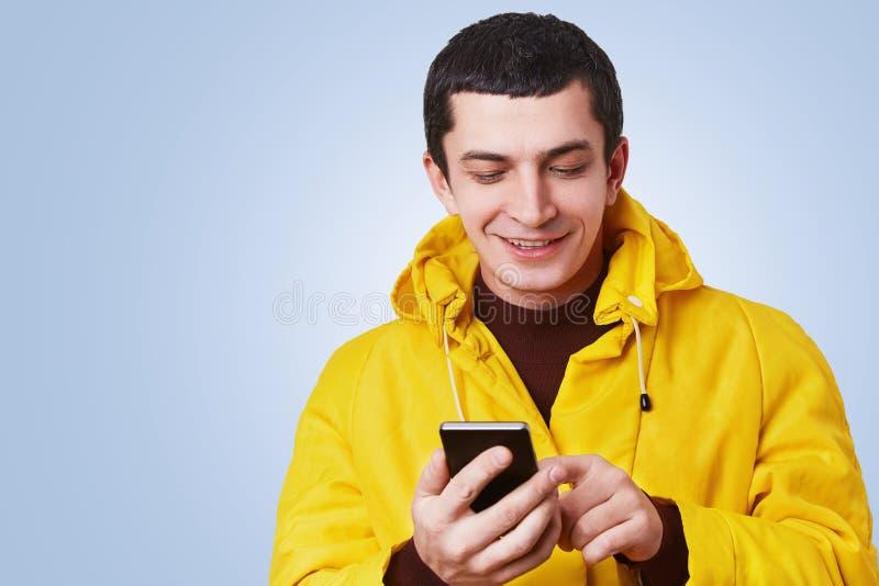 Portret rozochocony atrakcyjny młody człowiek używa nowożytnego telefon komórkowego, kipieli ogólnospołeczne sieci, uradowani czy obrazy stock