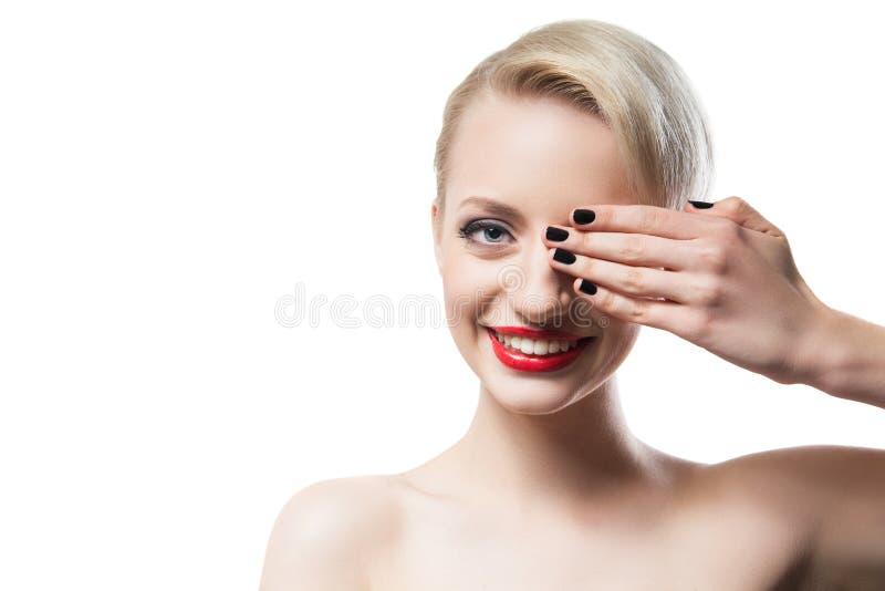 Portret rozochocony blondynka modela nakrycia oko z robiącą manikiur ręką zdjęcia stock