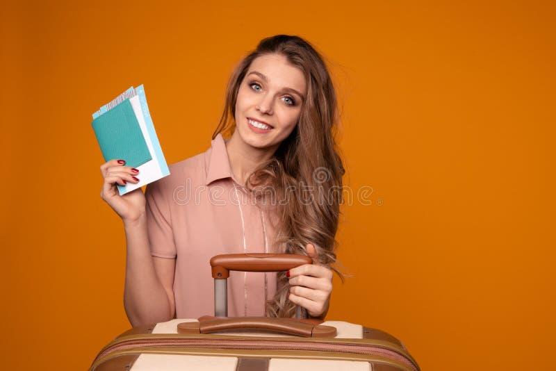 Portret rozochocony młodej kobiety mienia paszport z biletami siedzi blisko walizki zdjęcie royalty free