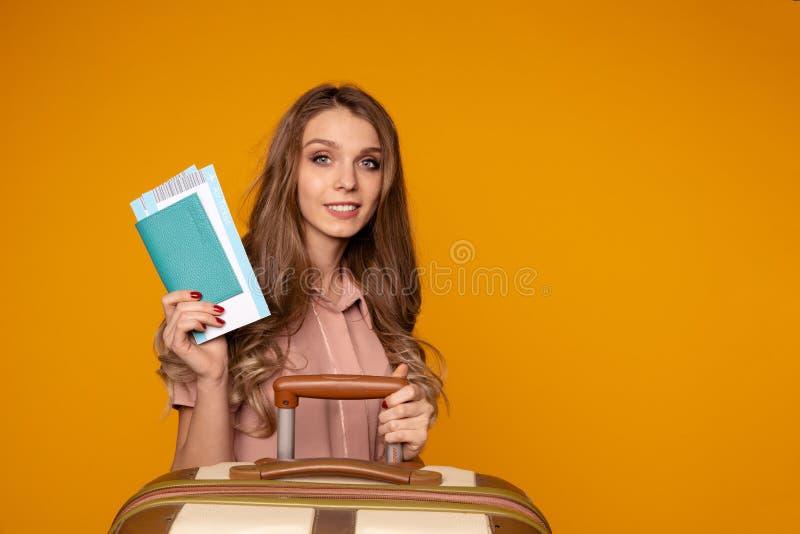 Portret rozochocony młodej kobiety mienia paszport z biletami siedzi blisko walizki zdjęcie stock