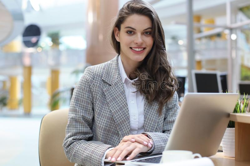 Portret rozochocony młody bizneswomanu obsiadanie przy stołem w biurowej i patrzeje kamerze fotografia royalty free