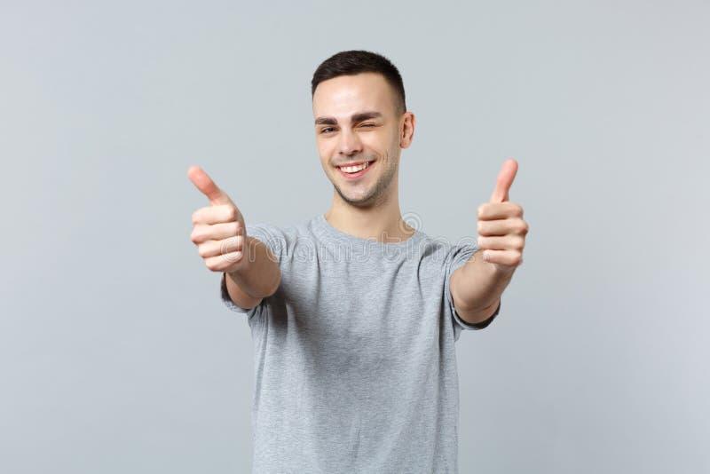 Portret rozochocony mruganie młody człowiek stoi aprobaty odizolowywać na popielatej ścianie i pokazuje w przypadkowych ubraniach zdjęcie stock