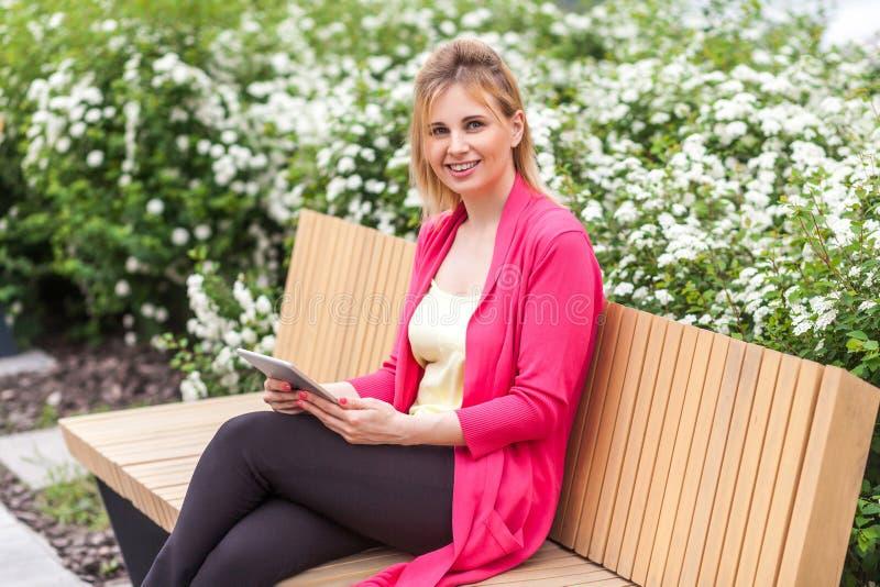 Portret rozochocony piękny młody bizneswoman w elegancja stylu obsiadaniu w ławce na parku, mienie pastylka z toothy uśmiechem obrazy royalty free