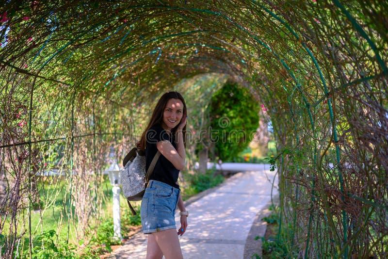 Portret rozochocony uśmiechnięty dziewczyny odprowadzenie w parku zielone rośliny zdjęcia stock