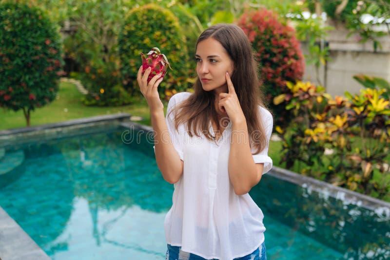 Portret rozważna dziewczyna z długie włosy mienie smoka owoc, pitaya w jej ręce, myśleć łasowanie lub no jeść go, obraz stock