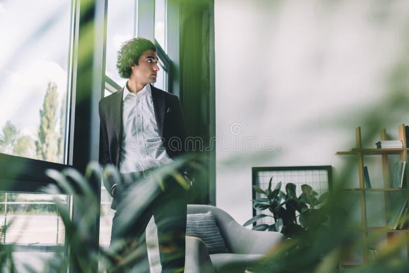portret rozważna biznesmen pozycja przy nadokiennym i patrzeć daleko od fotografia royalty free