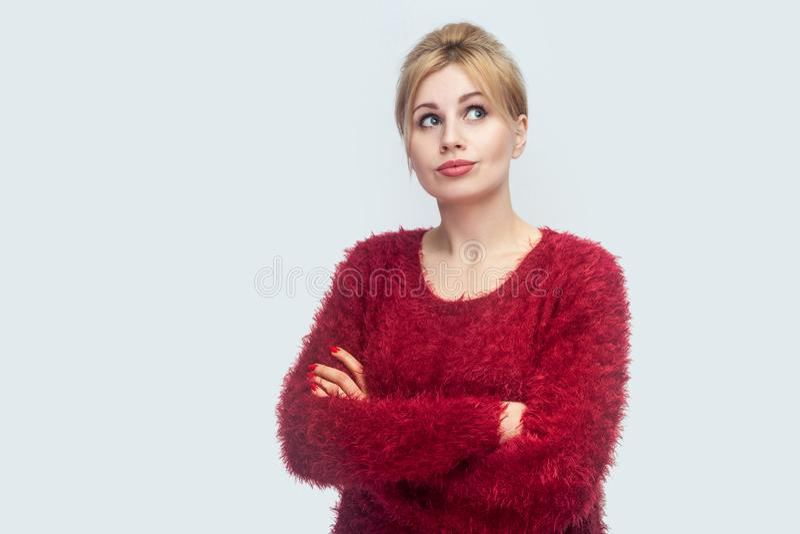Portret rozważna piękna młoda blond kobieta w czerwonej bluzki pozycji z krzyżować rękami i główkowaniem, patrzejący oddalony co  zdjęcie royalty free