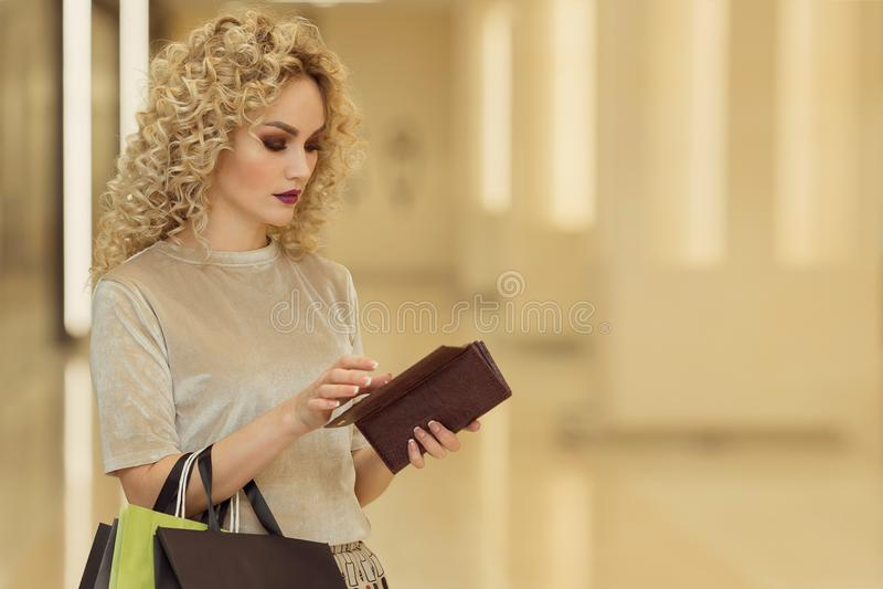 Portret rozważnego pięknego osoby mienia otwarty portfel z zadumanym wyrażeniem w centrum handlowym z sklepami na tle fotografia stock