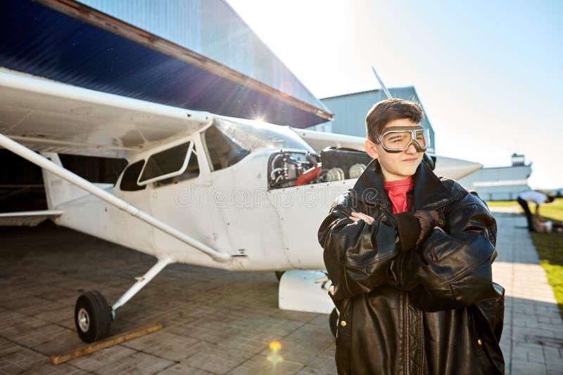 Portret rozważni chłopiec stojaki w wielkiej skóra pilota kurtce fotografia royalty free
