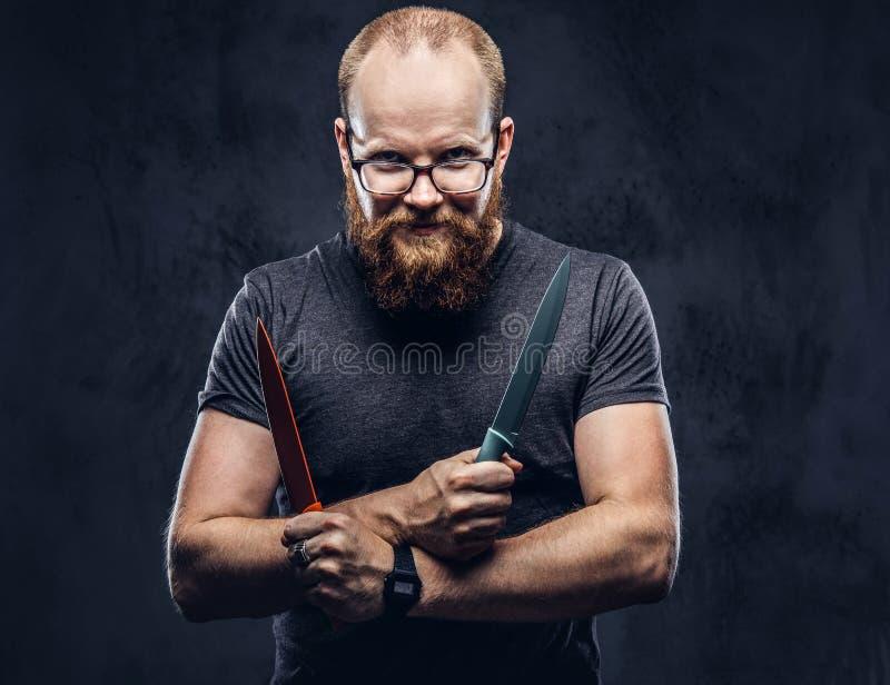 Portret rudzielec brodata samiec jest ubranym szkła ubierał w szarej koszulce, stoi z barwionymi stalowymi nożami w jego zdjęcia stock