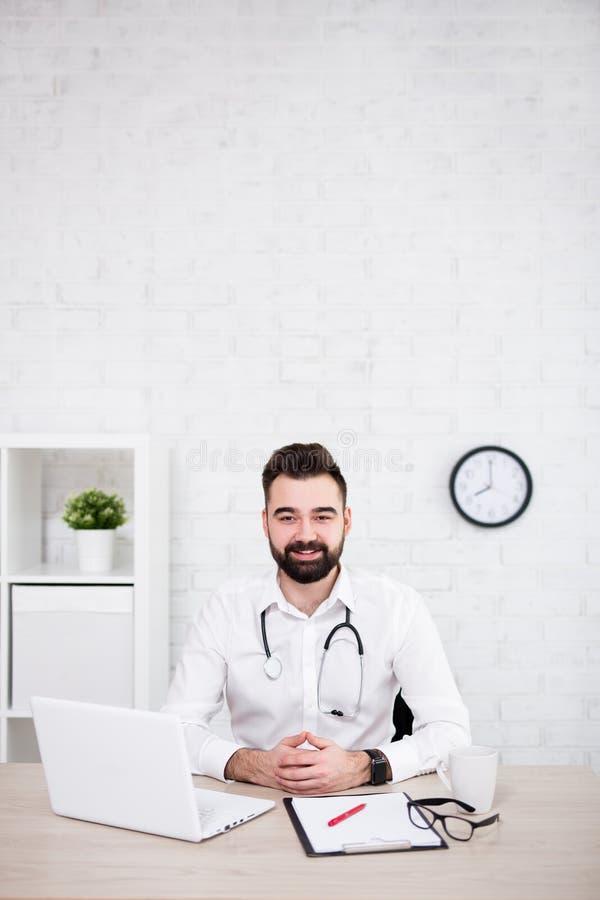 Portret samiec doktorski używa laptop w biurze - odbitkowa przestrzeń nad białą ścianą z cegieł zdjęcie royalty free