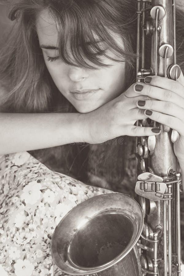 Portret in schemerige kleuren in de kleding van een jong meisje dat de kalmtezitting met saxofoon heeft gevonden stock fotografie