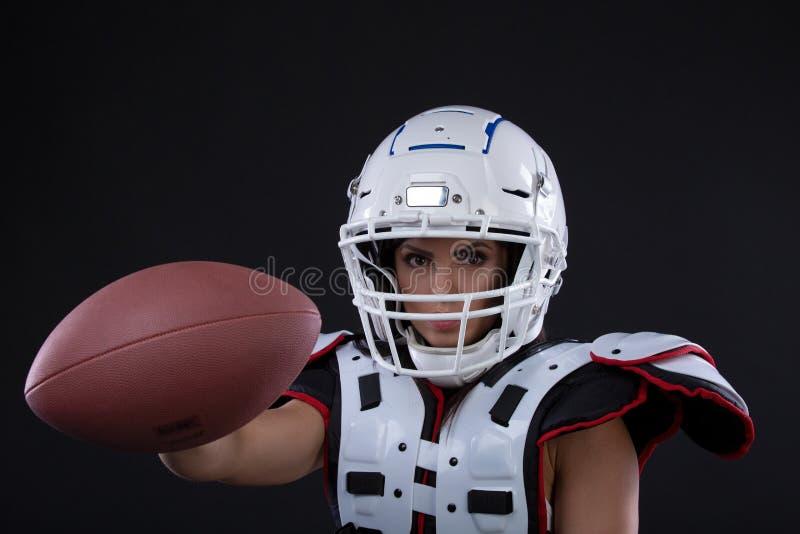 Portret seksowna atrakcyjna młoda dziewczyna silnie patrzeje przednią pozycję na czarnym bac w sporta stroju dla rugby z hełmem zdjęcie royalty free