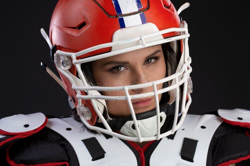 Portret seksowna atrakcyjna młoda dziewczyna z jaskrawym makijażem w sporta stroju dla rugby z hełmem na głowie silnie patrzeje zdjęcia stock