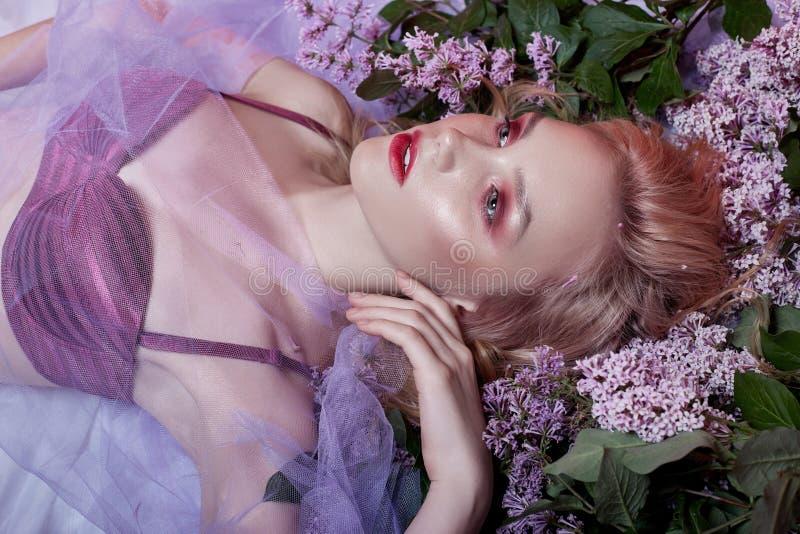 Portret seksowna blondynka w bieliźnie z jaskrawym makeup lying on the beach w lilym kwiacie Nikła blondynka, perfect długie włos obraz royalty free