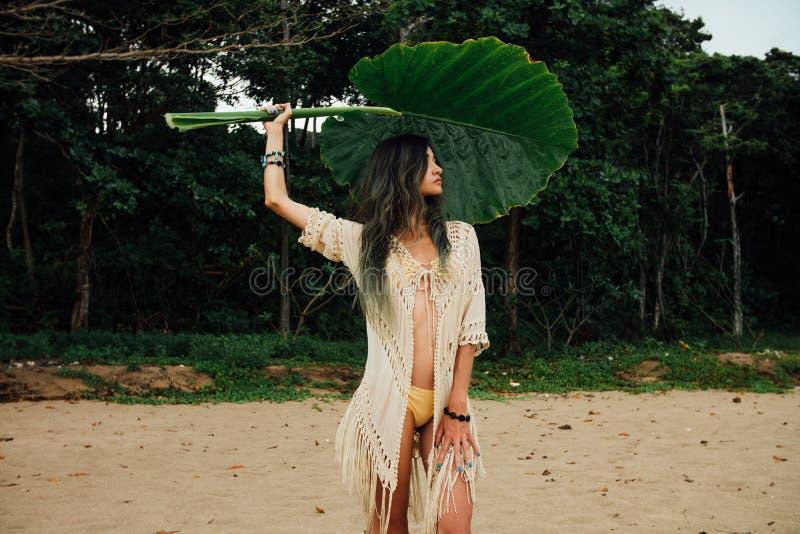 Portret seksowna młoda kobieta w bikini i tunika z wielkiego liścia tropikalnym drzewem fotografia stock