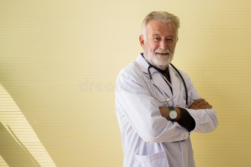 Portret senior lekarki krzyż i pozycja zbroi przyglądającą kamerę przy szpitala, Szczęśliwej i pozytywnej myślącą postawą, kopii  obrazy royalty free