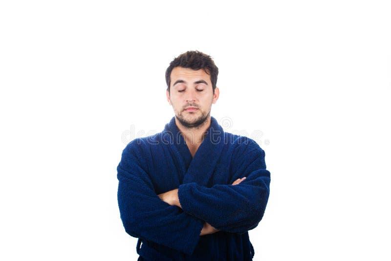 Portret sennego młodzieńca nosi niebieską szatę z zamkniętymi ramionami, czuć, że zmęczenie wymaga snu izolowanego na białym zdjęcia stock