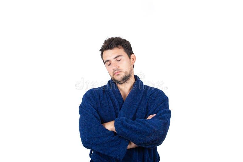 Portret sennego młodzieńca nosi niebieską szatę z zamkniętymi ramionami, czuć, że zmęczenie wymaga snu izolowanego na białym zdjęcie royalty free