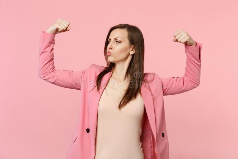 Portret silna śmieszna młoda kobieta w kurtek podmuchowych wargach, seansów bicepsy, mięśnie na pastelowych menchii ścianie zdjęcie royalty free