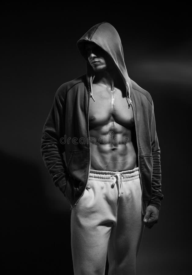 Portret silnej zdrowej przystojnej Sportowej mężczyzna sprawności fizycznej Wzorcowy pozować blisko zmroku - szarości ściana obraz stock